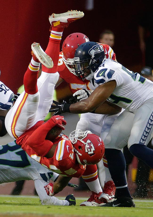 Knile Davis of the Kansas City Chiefs is upended by Dion Bailey of the Seattle Seahawks.