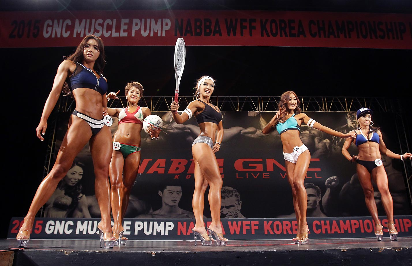 Bodybuilders pose for judges during the NABBA WFF Korea Championship in Seoul, South Korea.