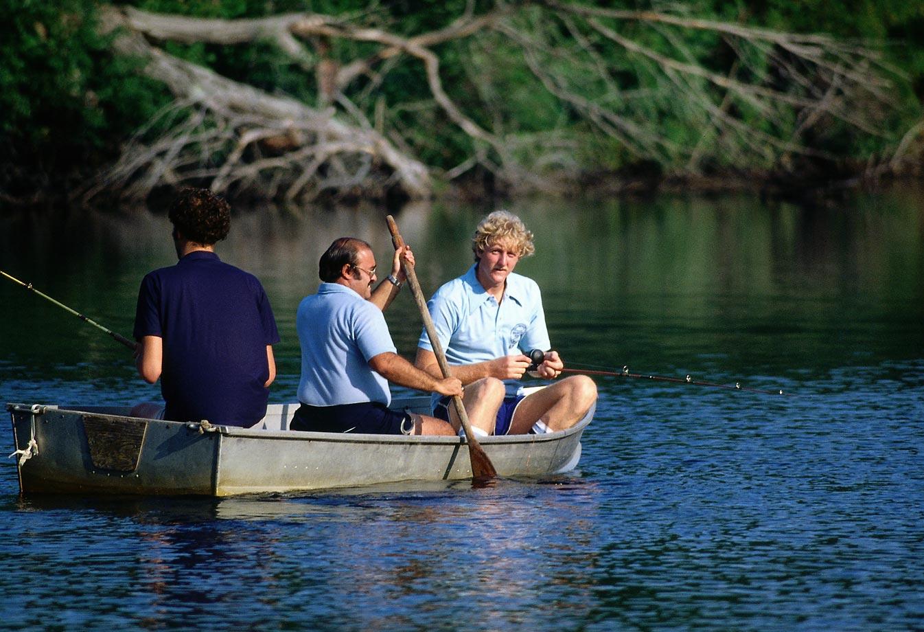 Larry Bird of the Boston Celtics enjoying fishing on the lake while at rookie camp in Boston.
