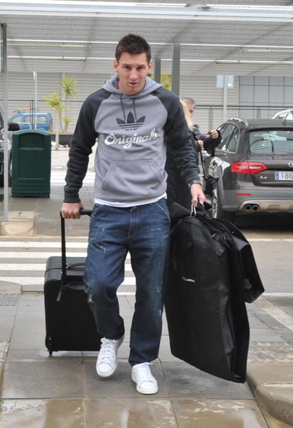 Messi glides his way through a Barcelona airport. (Getty Images)