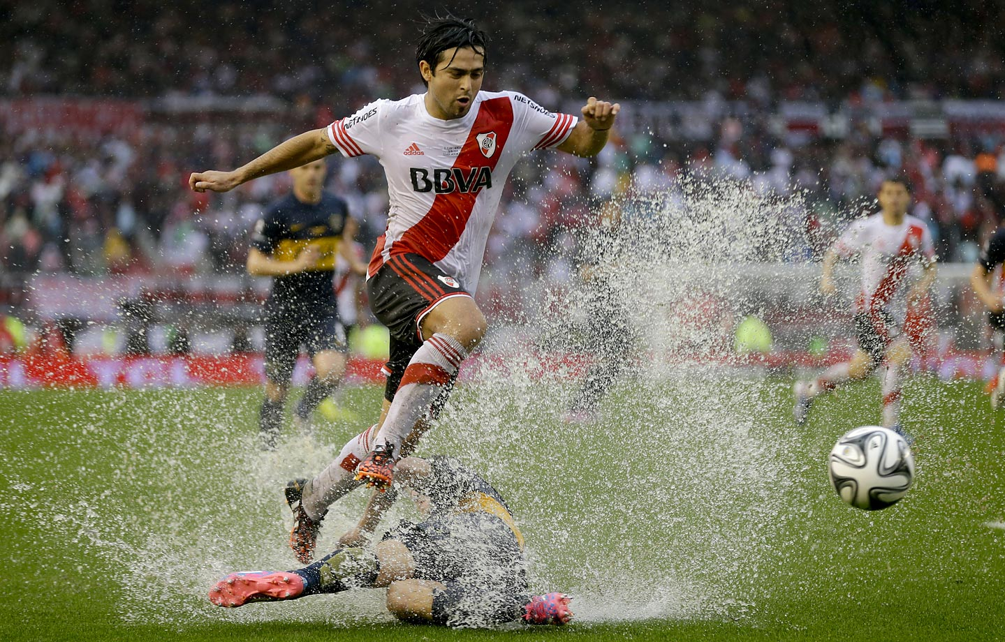 River Plate's Leonardo Pisculichi fights for the ball with Boca Juniors' Nicolas Colazo during a rainy Argentine league soccer match in Buenos Aires.