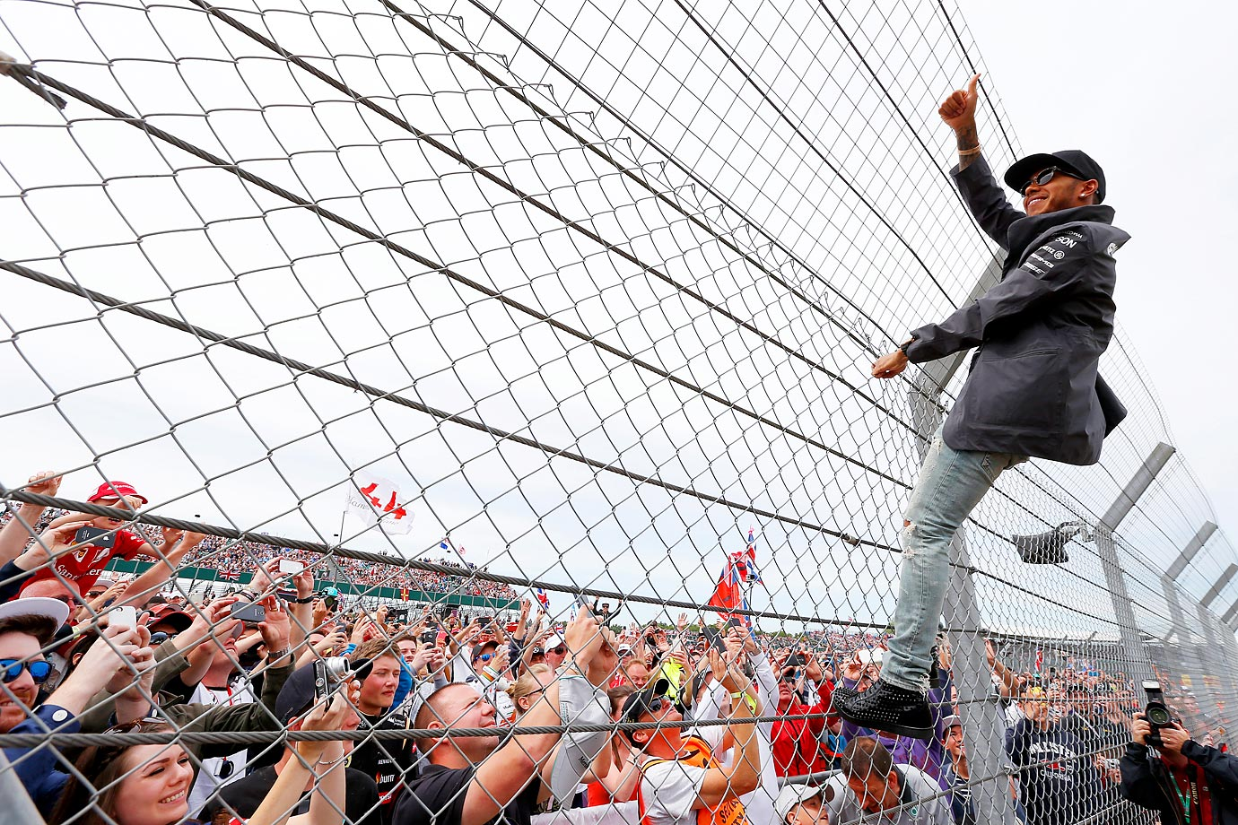 Lewis Hamilton climbs the fence before the Formula One Grand Prix of Great Britain.