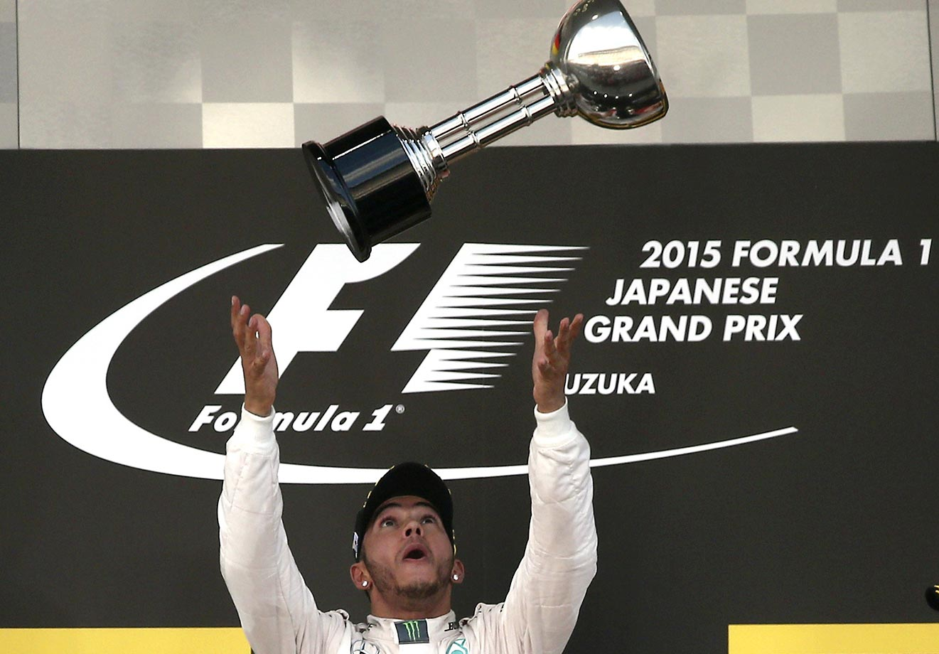 Lewis Hamilton throws the trophy into the air after winning the Japanese Formula One Grand Prix.