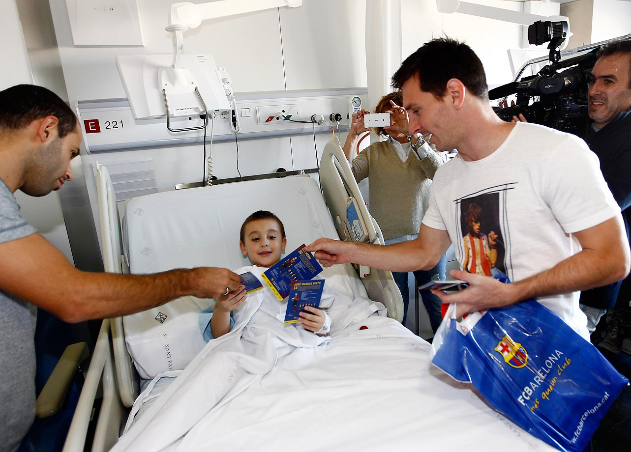 Barcelona footballers Lionel Messi and Javier Mascherano give presents to a patient during a charity visit to Sant Pau Hospital in Barcelona.