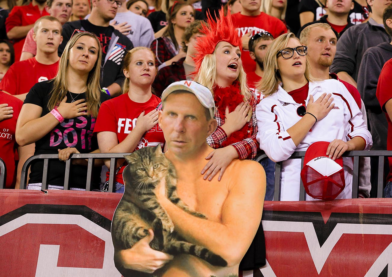 Mackenzie Huber of the University of South Dakota (red hair), who is the director of the Coyote Crazies, sings the Star Spangled Banner while holding a poster of a shirtless Bo Pelini holding a cat.