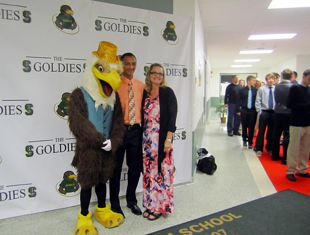 Seneca High student-athletes line the red carpet entrance to the Goldies to pose with the school mascot.