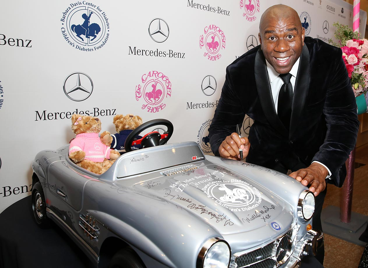 Magic Johnson autographs a Mercedes-Benz for auction at the Carousel of Hope Ball.
