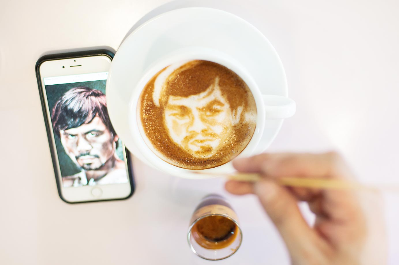 Filipino graphic artist Zach Yonzon sketches the face of Manny Pacquiao in the milk foam of a cup of coffee.