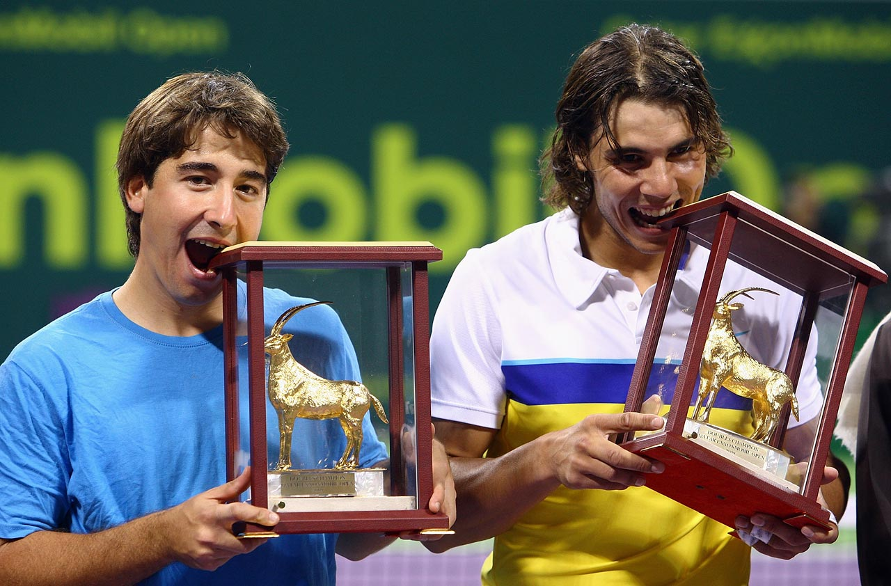 Marc Lopez and Rafael Nadal of Spain bite their trophies after defeating Daniel Nestor of Canada and Nenad Zimonjic of Serbia in the doubles final during the 2009 ATP Qatar Tennis Open in Doha, Qatar.
