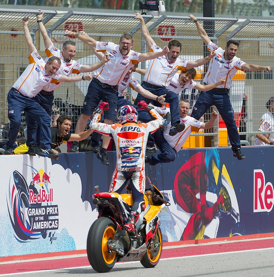Marc Marquez rides by and celebrates with his crew after winning the MotoGP Grand Prix race at the Circuit of the Americas in Austin, Texas.