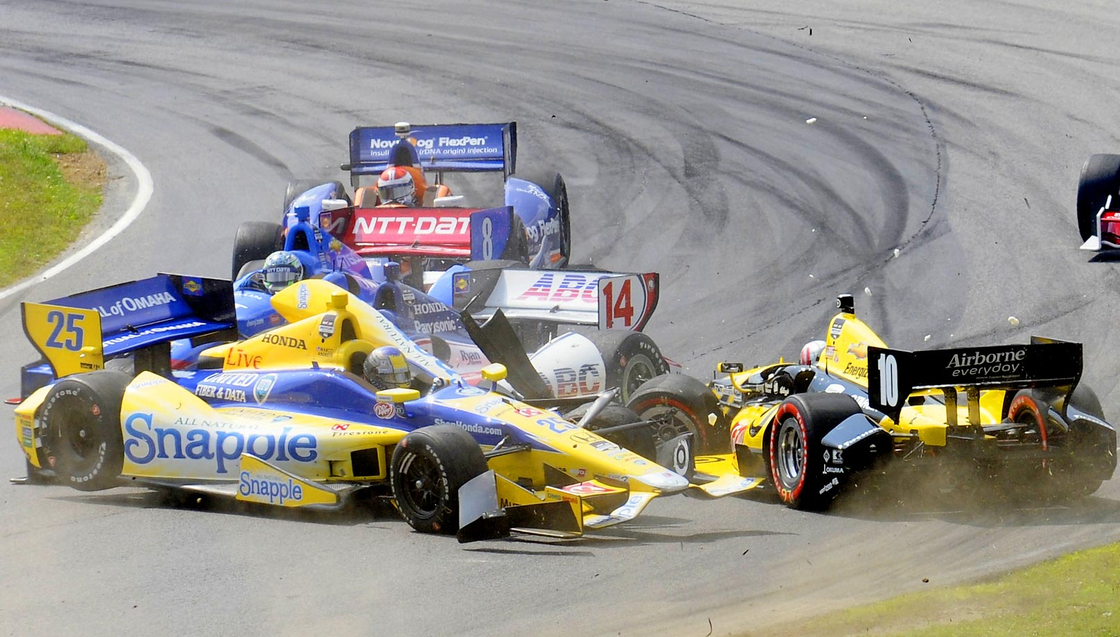 Marco Andretti (25) collides with Tony Kanaan (10), of Brazil, in a first lap crash during the IndyCar Honda Indy 200 auto racing at Mid-Ohio Sports Car Course in Lexington, Ohio Sunday, Aug. 3, 2014, while Takuma Sato (14), of Japan, and Ryan Briscoe (8), of Australia, try to avoid the crash.