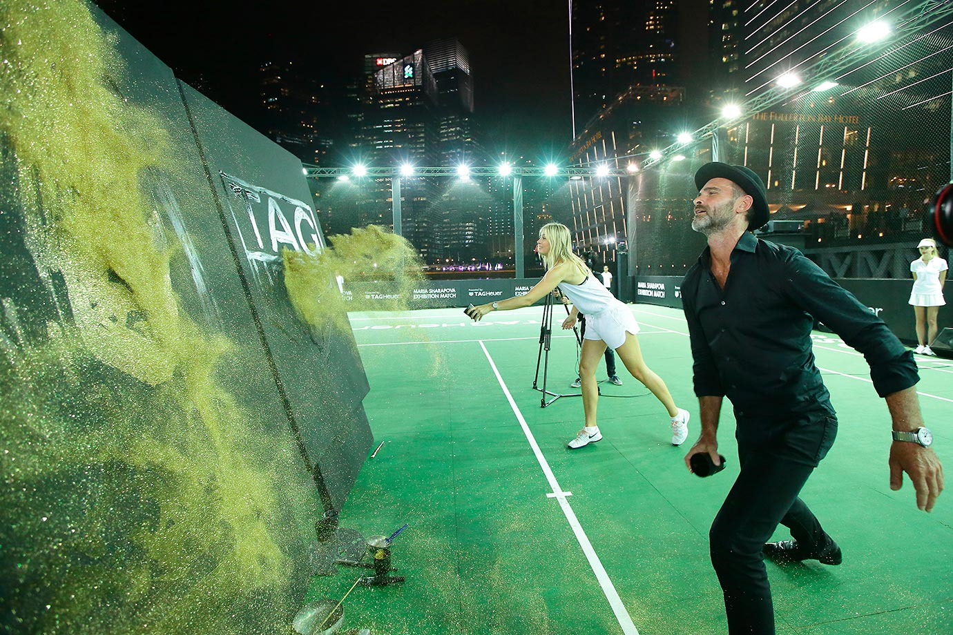 Maria Sharapova and speed painting artist Michael Raivard throw gold dust to reveal a portrait during a Maria Sharapova exhibition match in Singapore.