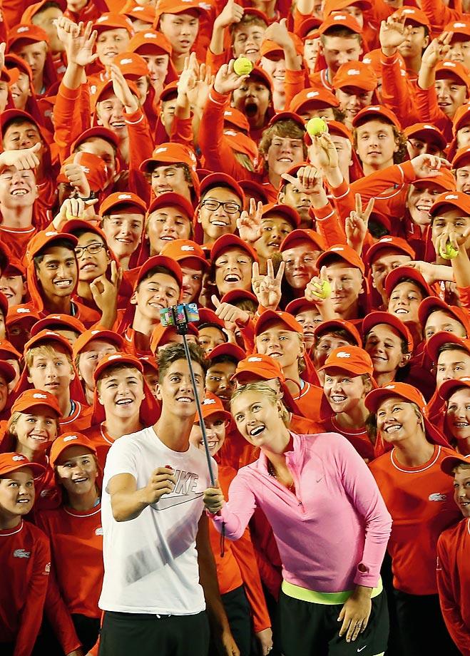 Thanasi Kokkinakis and Maria Sharapova take selfies with the ball kids of the Australian Open.