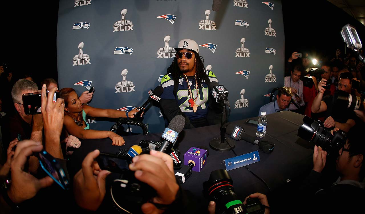Running back Marshawn Lynch sits at his podium during a Super Bowl XLIX media availability session on Wednesday.