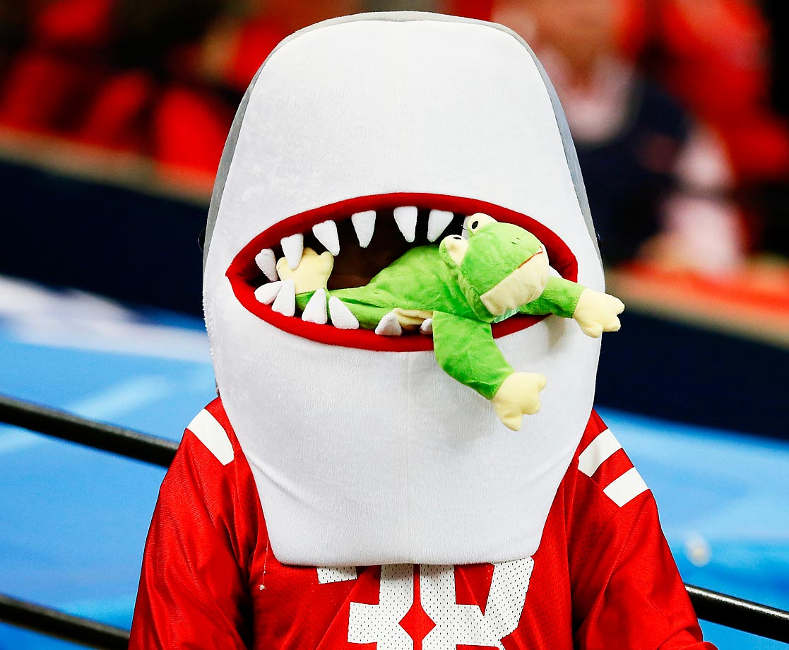 An Ole Miss Rebels fan in costume gobbles up a frog during the Chik-fil-A Peach Bowl between the TCU Horned Frogs and the Ole Miss Rebels.