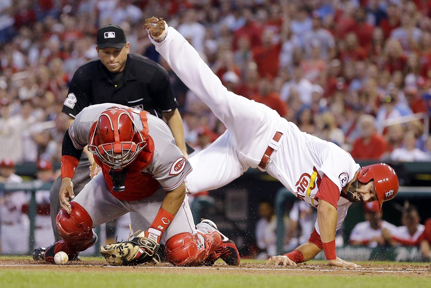Matt Carpenter of the Cardinals is safe as he flips over Brayan Pena of the Reds.