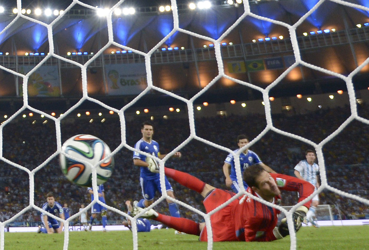 Bosnia-Hercegovina's goalkeeper Asmir Begovic fails to stop Lionel Messi's goal during a Group F football match.