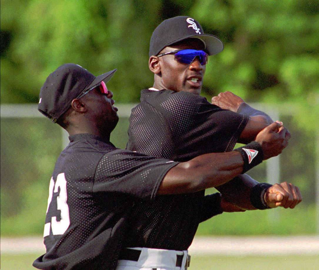 Michael Jordan gets help stretching his arm from fellow outfielder Mike Cameron during the first day of the White Sox Instructional League workouts in Sarasota, Fla., on Sept. 23, 1994.