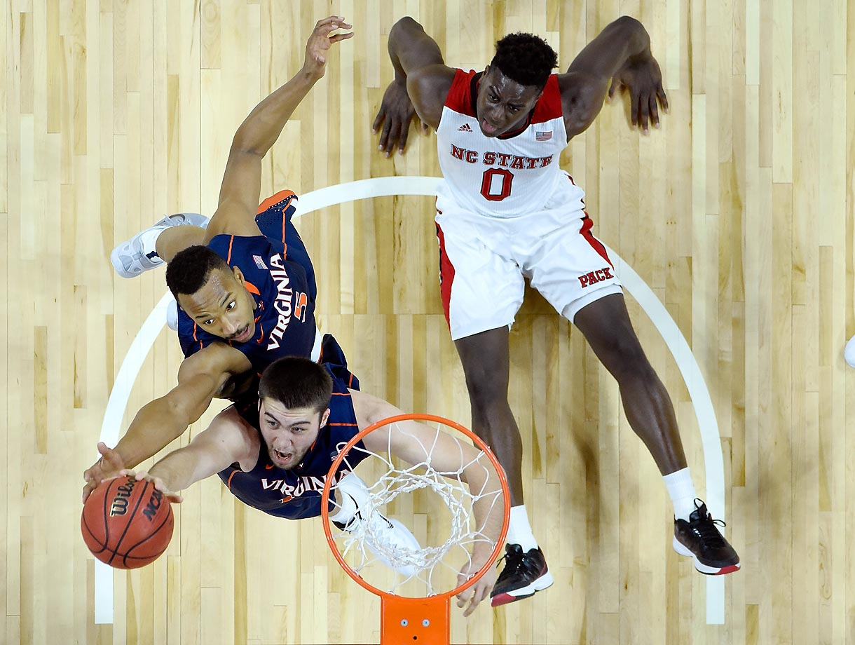 Mike Tobey (10) and Darion Atkins (5) of the Virginia Cavaliers battle Abdul-Malik Abu of the North Carolina State Wolfpack for a rebound. Virginia won 51-47.