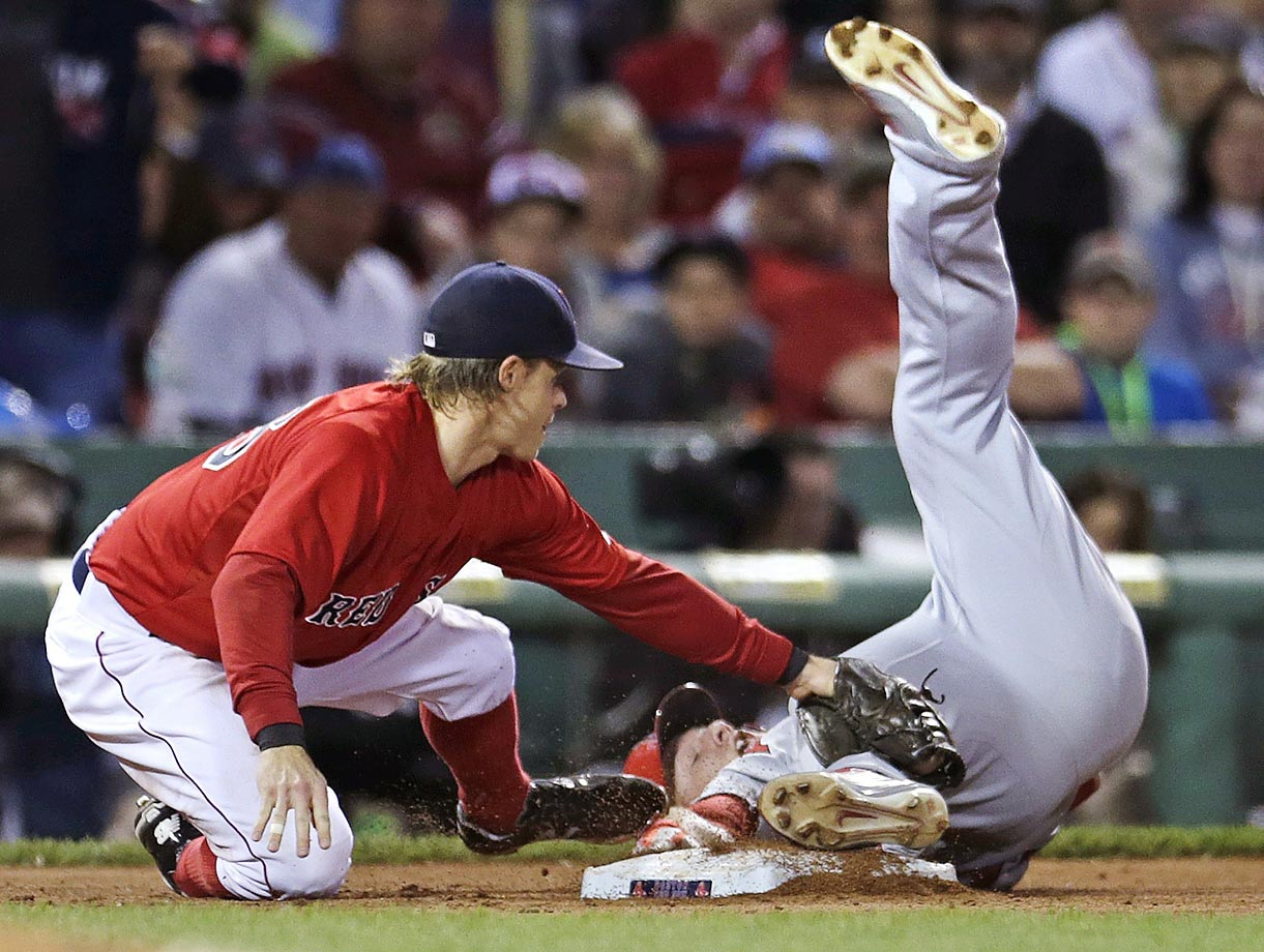 Mike Trout keeps his foot and hand firmly on third base as Brock Holt of the Red Sox makes the tag on a stolen base. Trout was initially called out, but the play was reversed after video review.