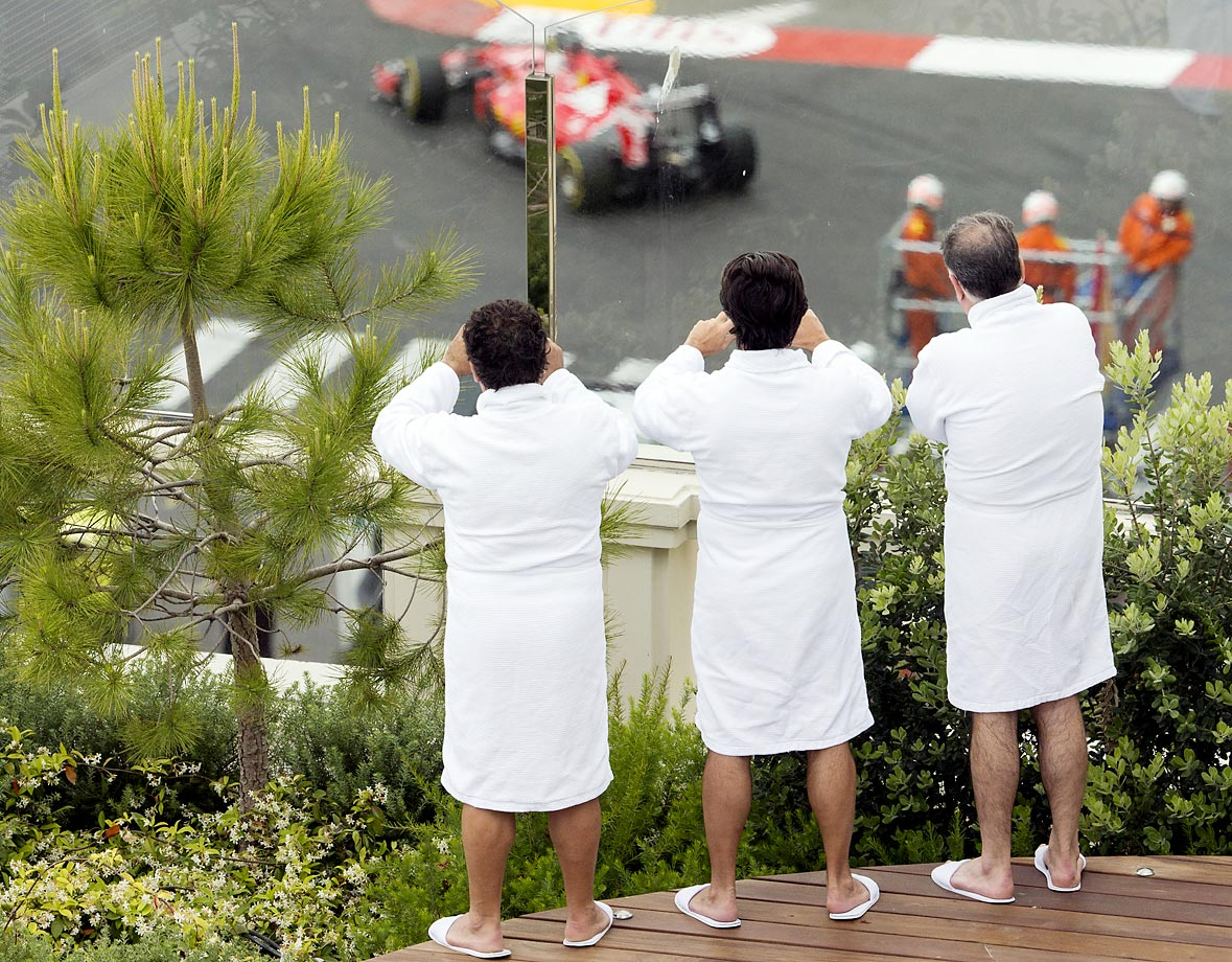 Men wearing bathrobes watch the qualifying session at the Monaco racetrack. The Formula One Grand Prix of Monaco was held on Sunday.