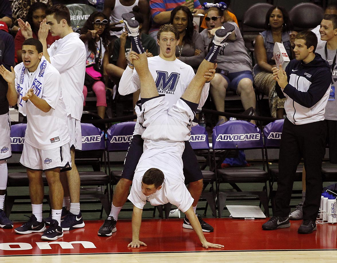 The Monmouth Hawks perform a scissor handstand after making a basket in the second half of the 2015 Advocare Invitational third place game against USC. Monmouth defeated USC 83-73.