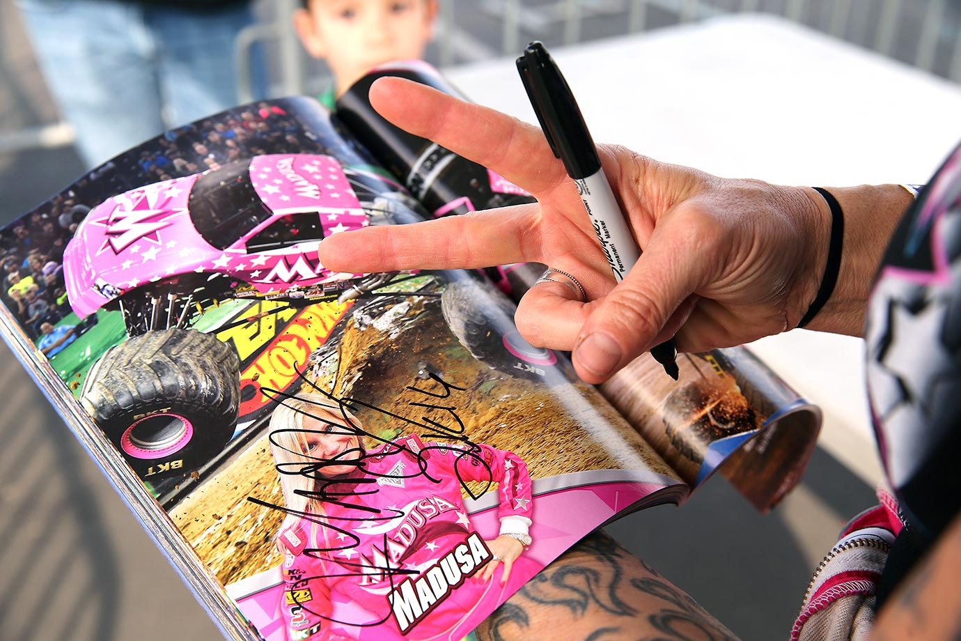 Madusa signs an autograph in the Monster Jam program for a fan before the competition.