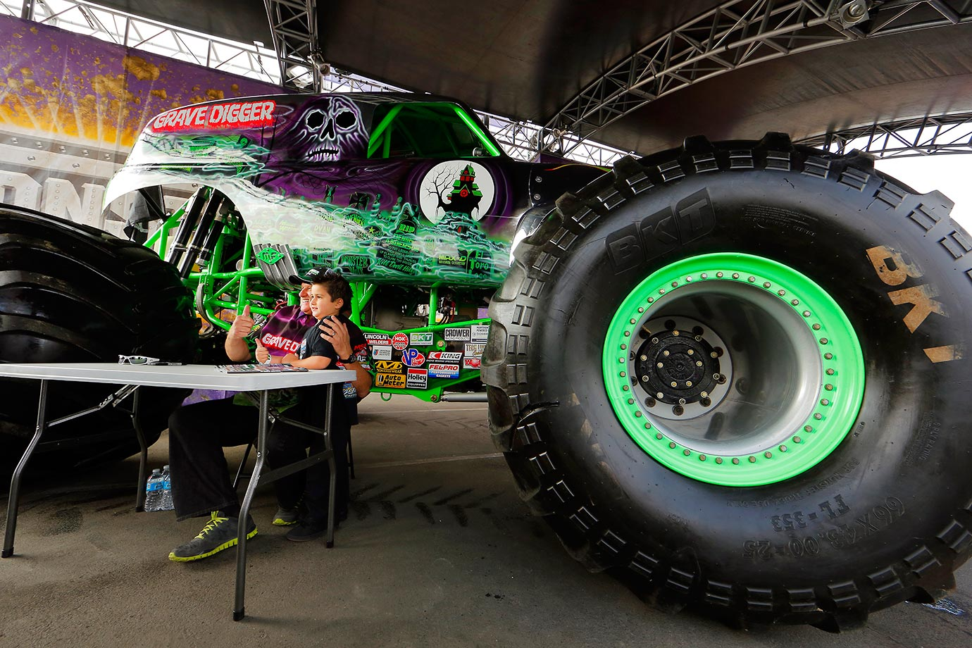 Dennis Anderson, monster truck driver of World Finals Champion 'Grave Digger, poses with a young fan next to his truck after signing autographs at the pre-race pit party.