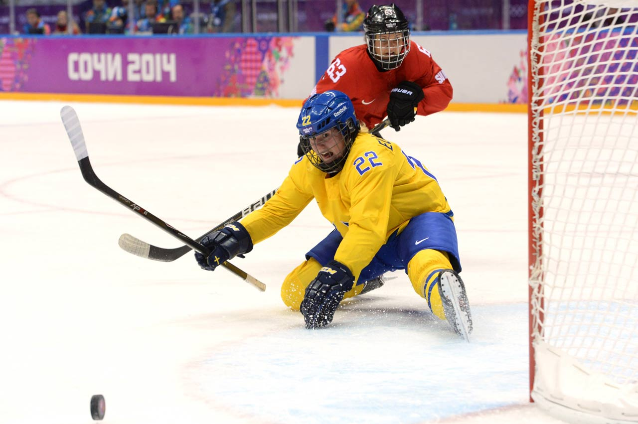 Sweden's Emma Eliasson watches in vain as the puck sails by while Switzerland's Anja Stiefel looks on.