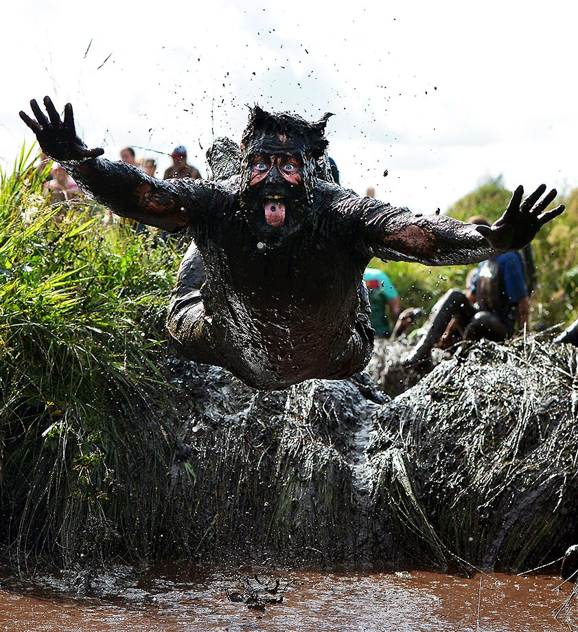 A competitor jumps head first into a mud pool at the Mud Madness race in Northern Ireland.