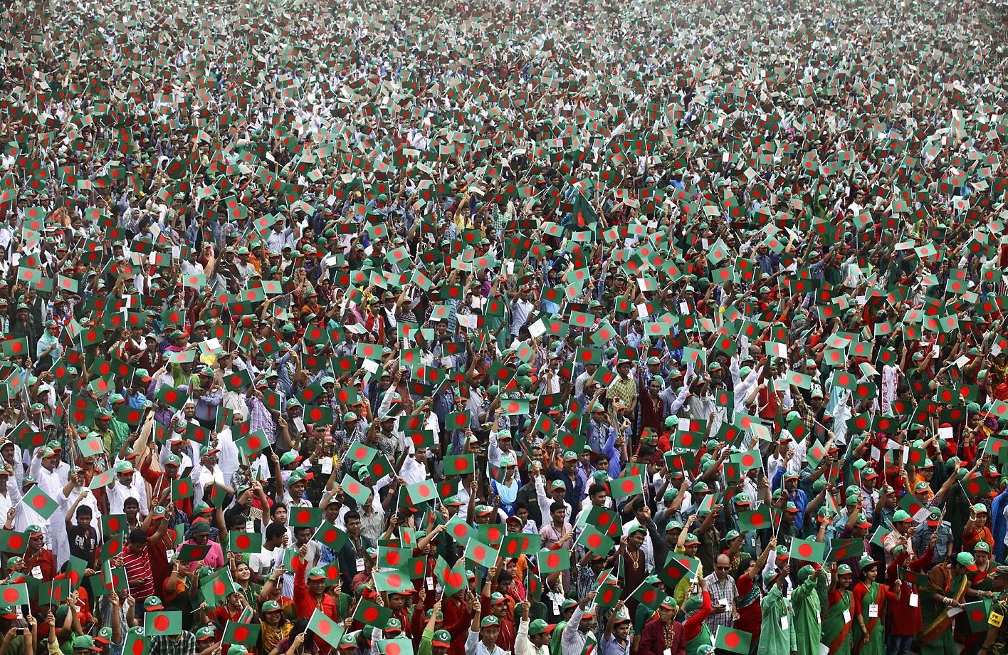 Bangladeshis wave their national flags as they gather at the National Parade Ground to create a Guinness world record of most people singing the national anthem in unison on March 26, 2013.