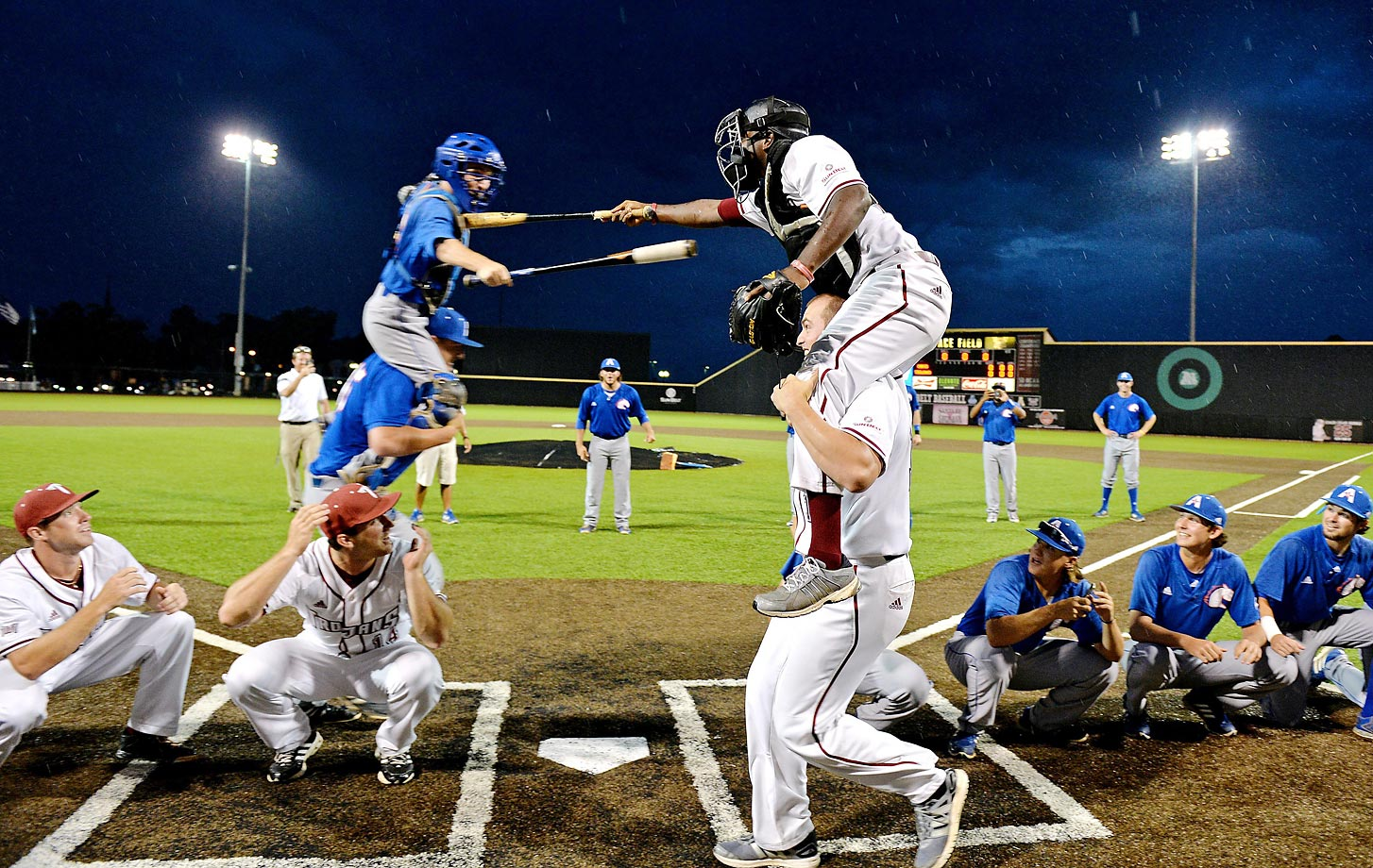 Troy and Texas-Arlington players joust during a weather delay at an NCAA college baseball game in Troy, Ala.