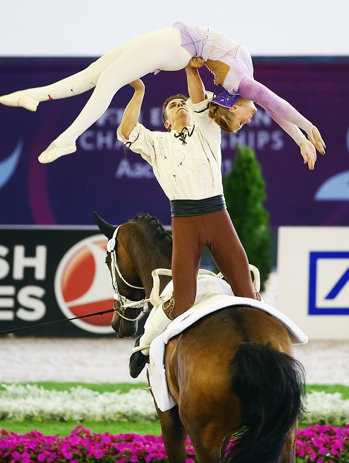 Gera-Marie Gruen and Justin van Gerven of Germany perform during the Vaulting Pas de Deux freestyle test at the FEI European Equestrian Championships in Aachen, Germany.