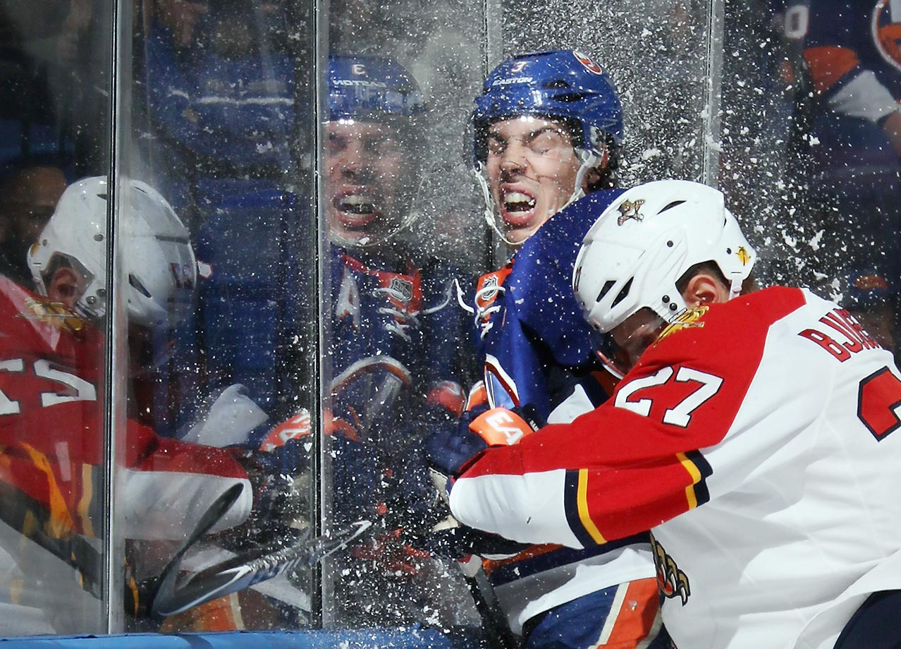Travis Hamonic of the New York Islanders is smashed into the glass by Nick Bjugstad of the Panthers.