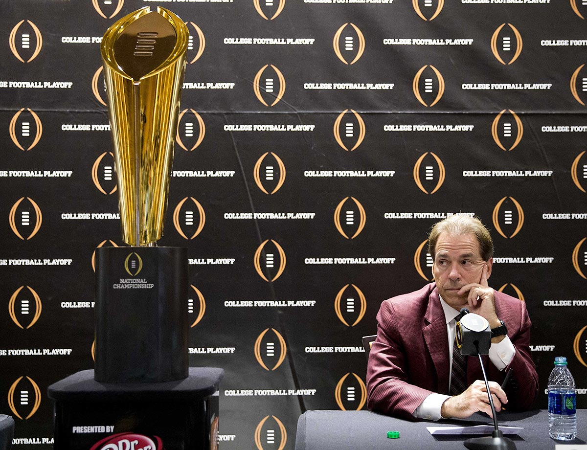 Nick Saban of Alabama sits next to the championship trophy at the College Footbal Hall of Fame.