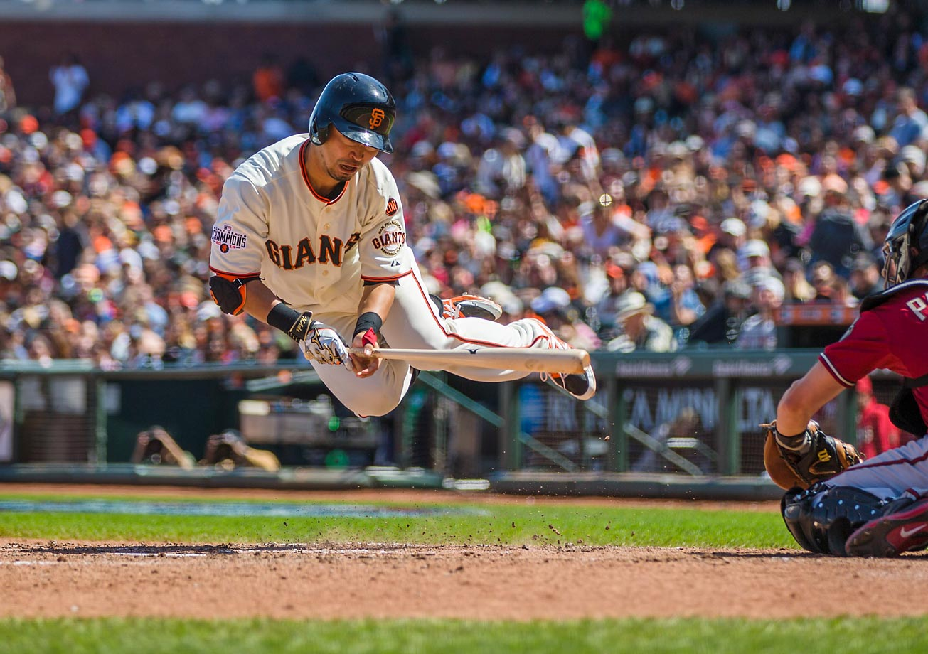 Nori Aoki of the Giants jumps to avoid getting hit by the ball in a game against the Diamondbacks.