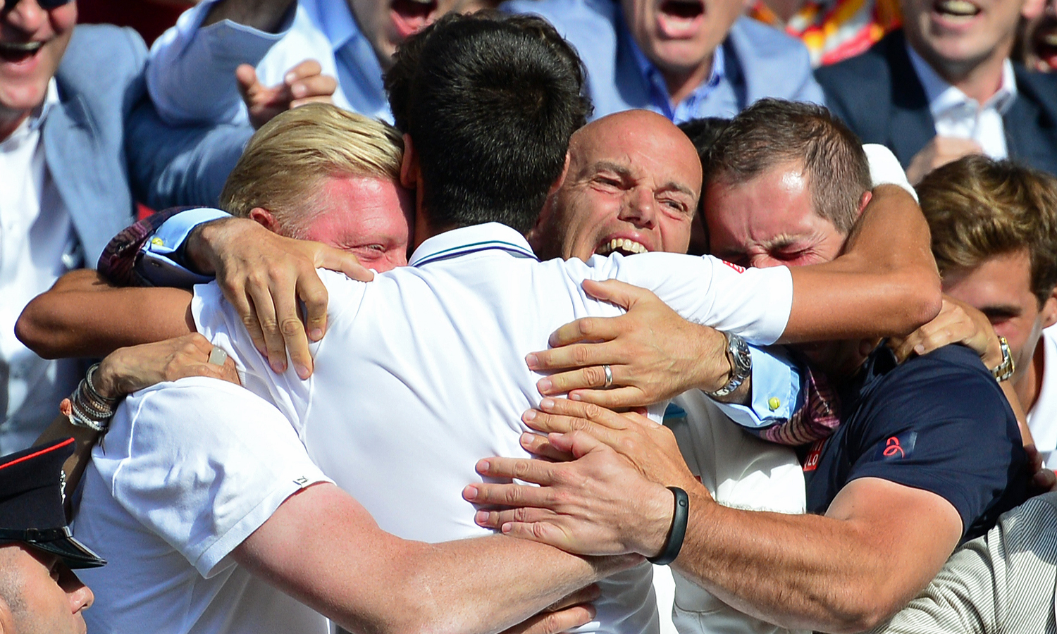 Novak Djokovic hugs his coach Boris Becker (left) and the rest of his team