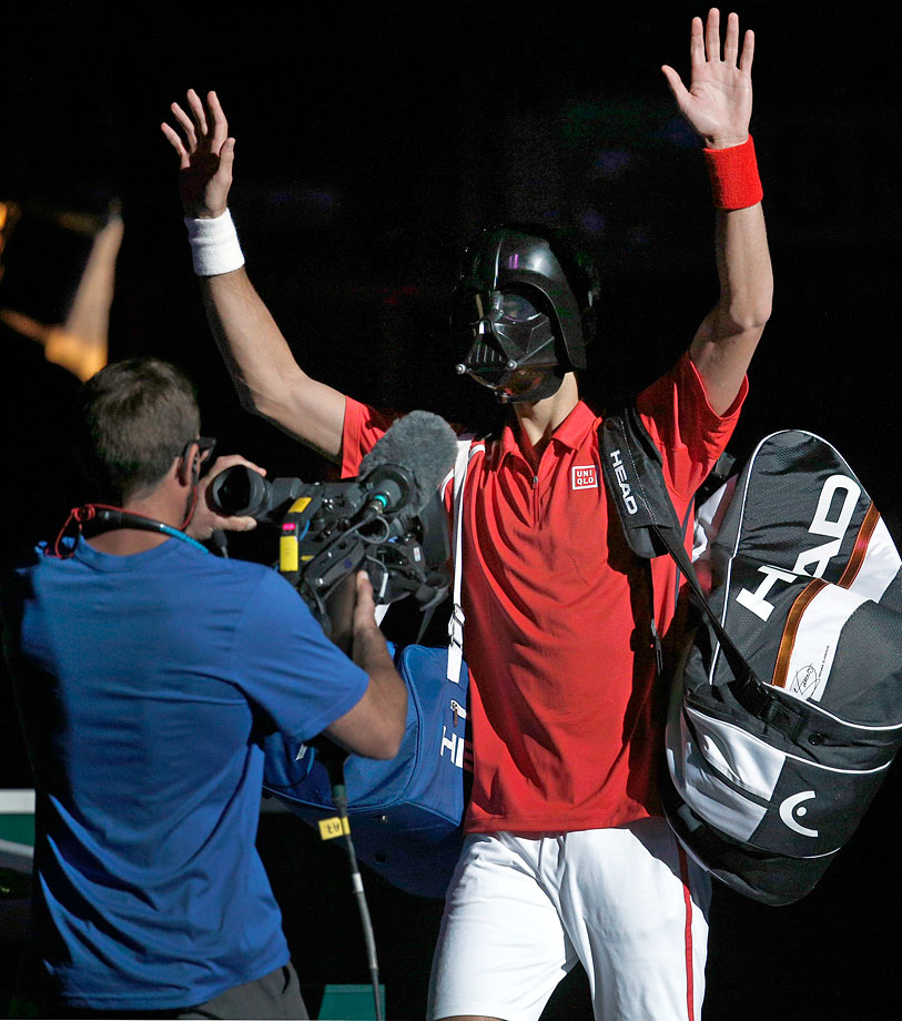 Novak Djokovic wears a Darth Vader mask and waves to the crowd as he arrives on court for his match against Sam Querrey on Oct. 31, 2012 at the Paris Tennis Masters tournament.