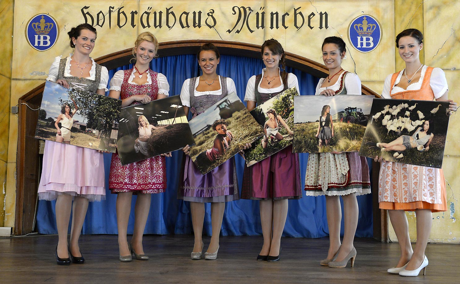 "Farm girls pose with their photos during the press presentation for the new ""Bavarian and Austrian Farm Girls' Calendar 2015"" at the Hofbraeuhaus beer hall in Munich."