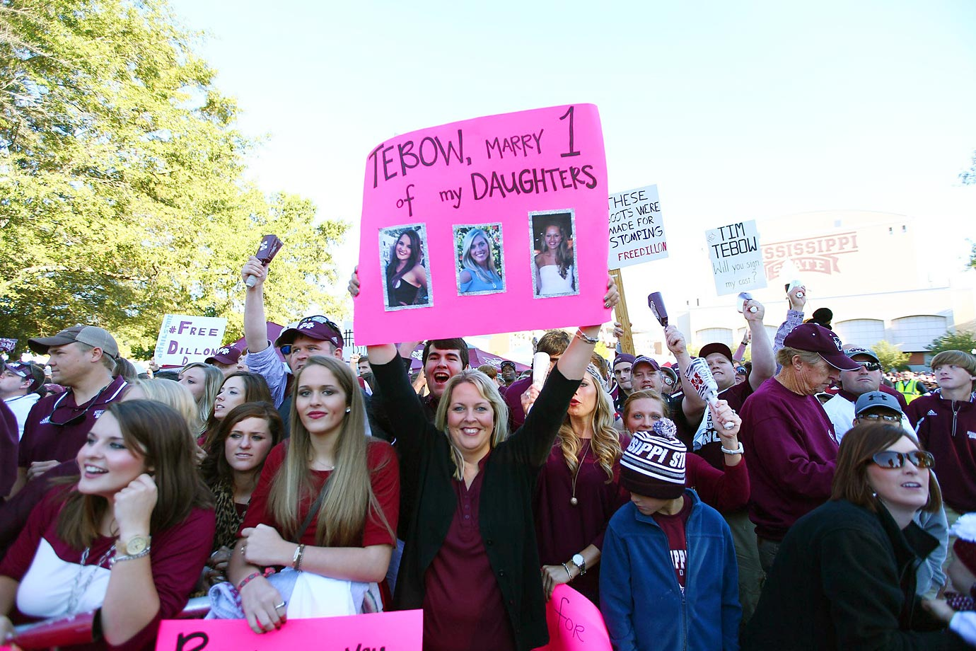 A mom at the Mississippi State game attempts to get Tim Tebow's attention.