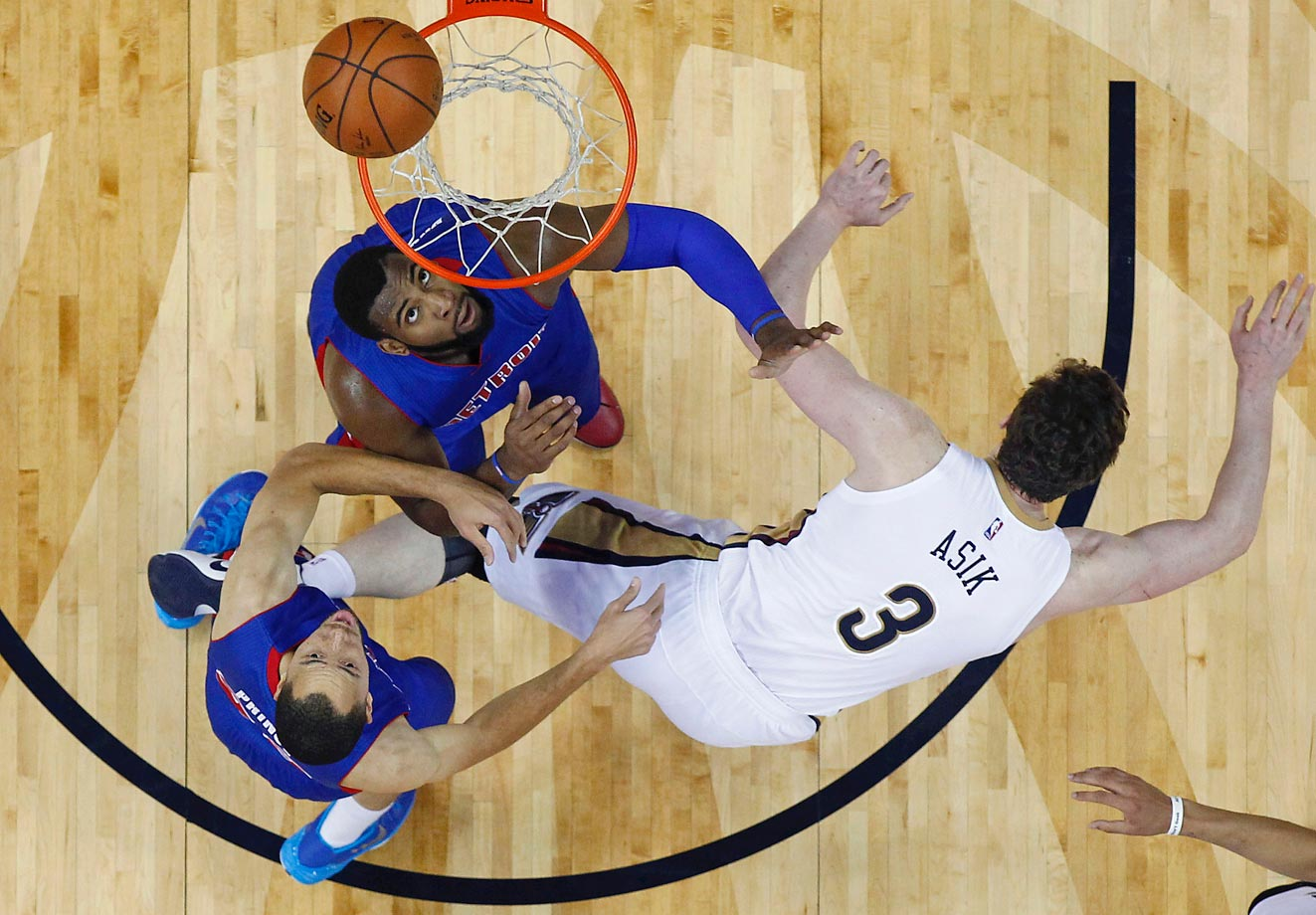 New Orleans Pelicans center Omer Asik falls over while attempting to drive to the basket against the Pistons Tayshaun Prince and Andre Drummond.
