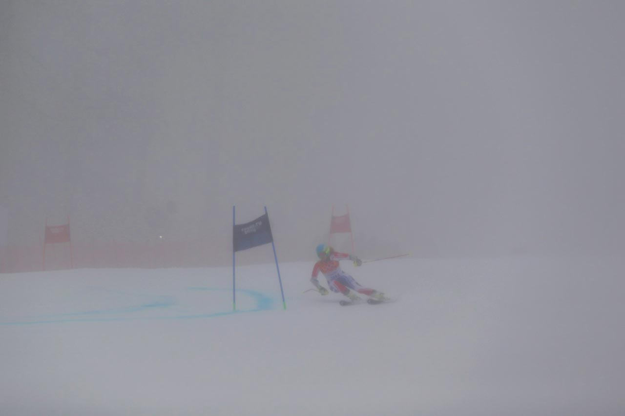 France's Anne-Sophie Barthet maneuvers her skis near a gate in a heavy fog.