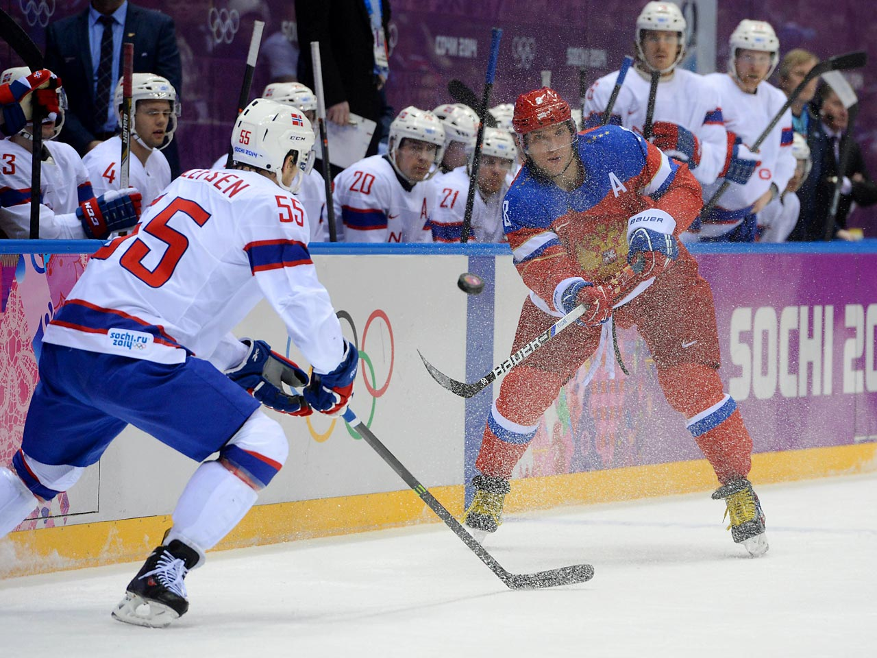 Russian Alexander Ovechkin hurls the puck down the ice as Ole-Kristian Tollefsen of Norway defends.