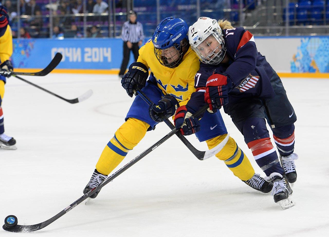Jocelyne Lamoureux of the U.S. fights for the puck against Sweden's Lina Backlin.