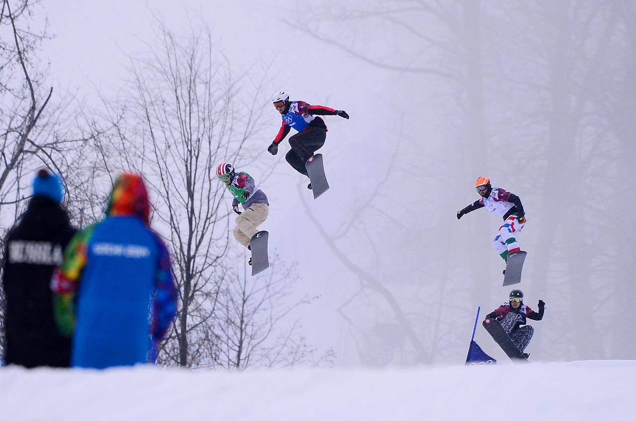 Competitors, including Alex Deibold of the United States (in green), compete in the men's snowboard cross finals. Deibold won the bronze medal.