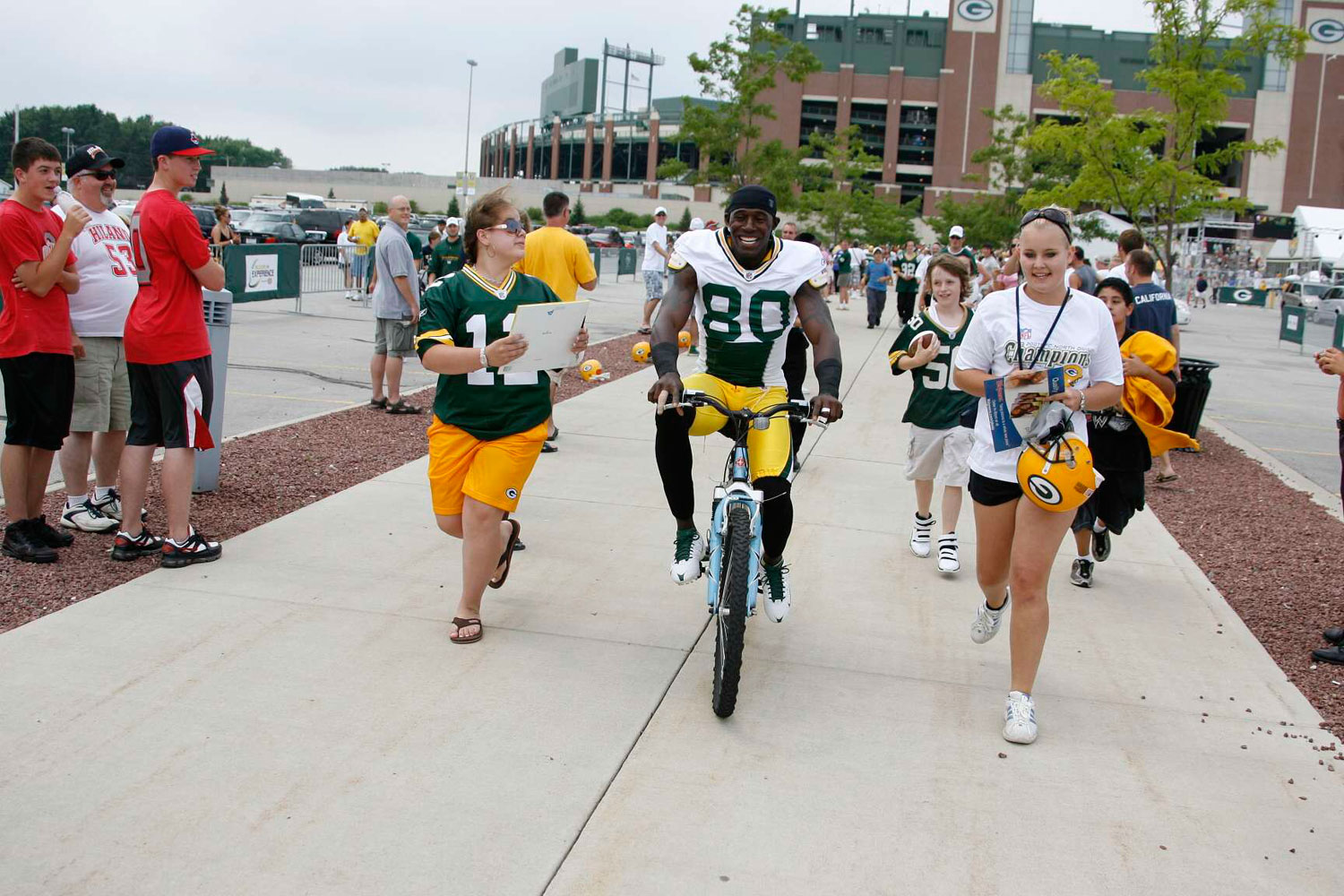 Former Green Bay Packers wide reciever Donald Driver bikes into training camp while fans follow in July 2008.