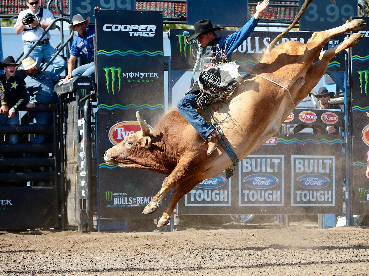 Emilio Resende attempts to ride Jeff Robinson's Percolator during the Bulls on the Beach event of the PBR Built Ford Tough series.