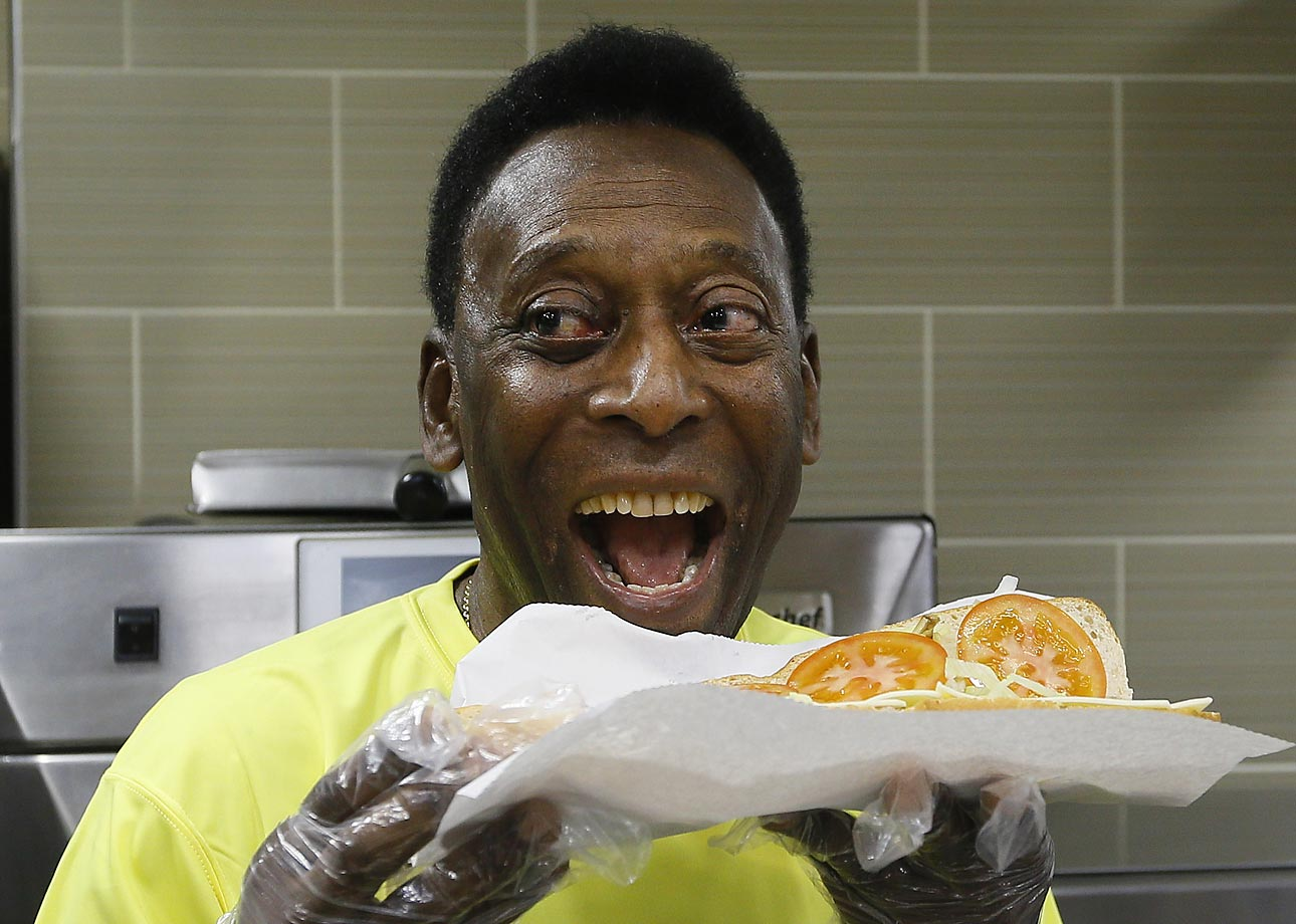 Pele poses with a sandwich that he prepared during a media event at a restaurant in London. Pele was in town to attend the match between Liverpool and Manchester United at Anfield Stadium in Liverpool.