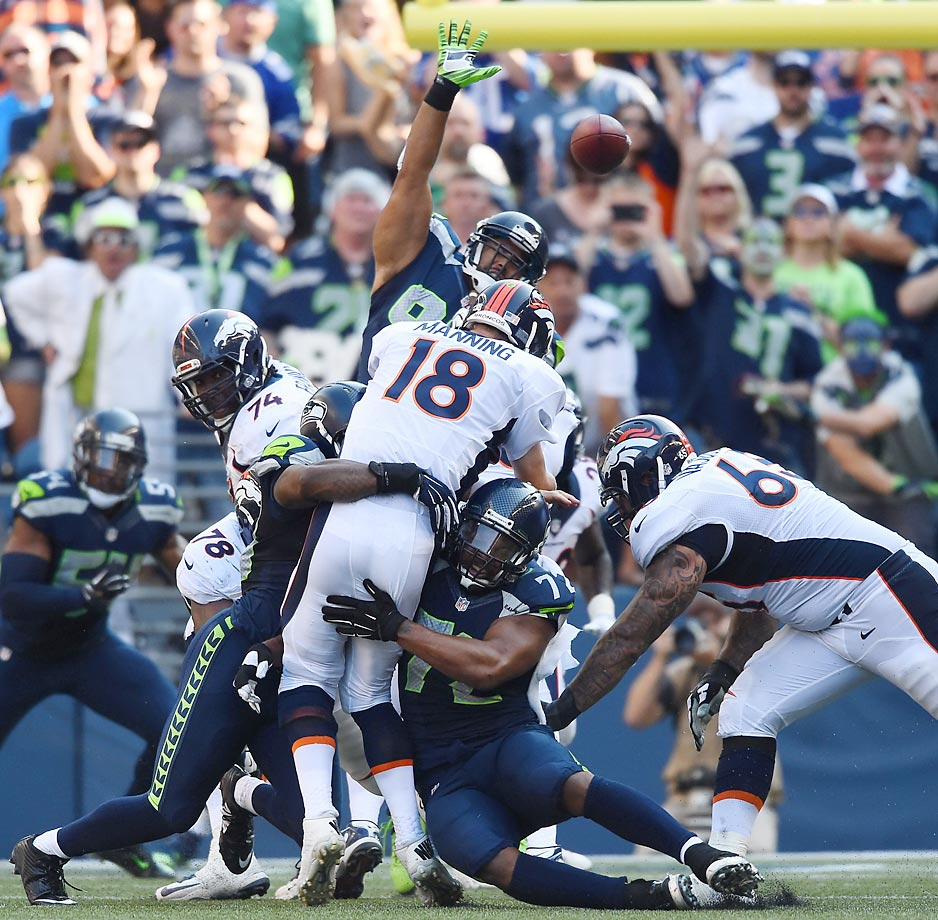 Peyton Manning is swarmed by the defense after letting the ball go during a 26-20 loss to the Seahawks.