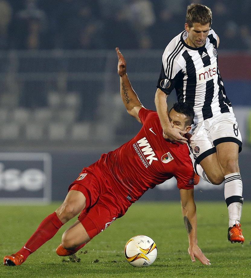 Raul Bobadilla of Augsburg (red) is challenged by Darko Brasanac of Partizan Belgrade during an Europa League Group L soccer match.